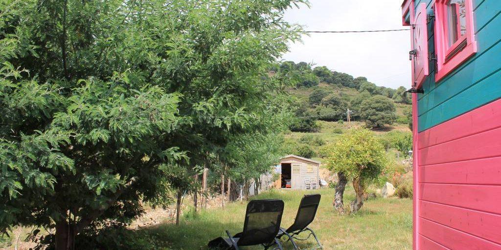 Chambres d'hotes U Cuventu di Paomia Cargese Corsica Frankrijk pipowagen roulotte tuin ligstoelen grasveld heuvels bomen