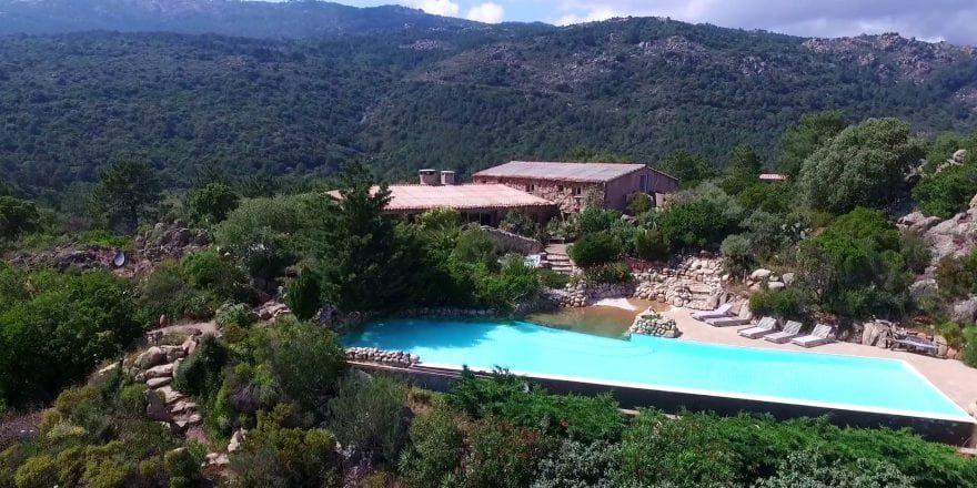 Ferme auberge Domaine de Piscia Corsica Frankrijk bovenaanzicht zwembad gebouwen bergen hellingen rotsen bos maquis