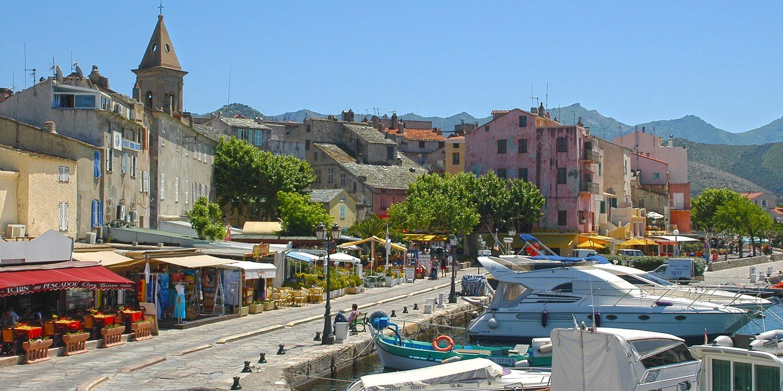 Hotel La Roya Saint-Florent Corsica Frankrijk stadje haven kade jachten vissersboot klokkentoren-min