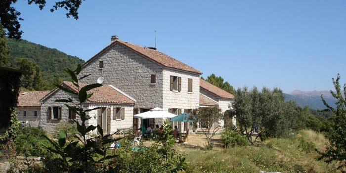 Ferme Auberge Domaine Aravaina Levie Alta Rocca Corsica Frankrijk façade gebouw terras parasols