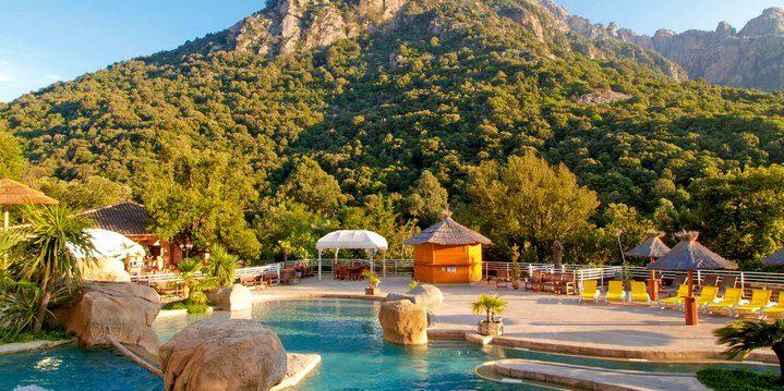 Camping Les Oliviers Porto Ota Corsica Frankrijk zwembad ligbedden bergen namiddagzon