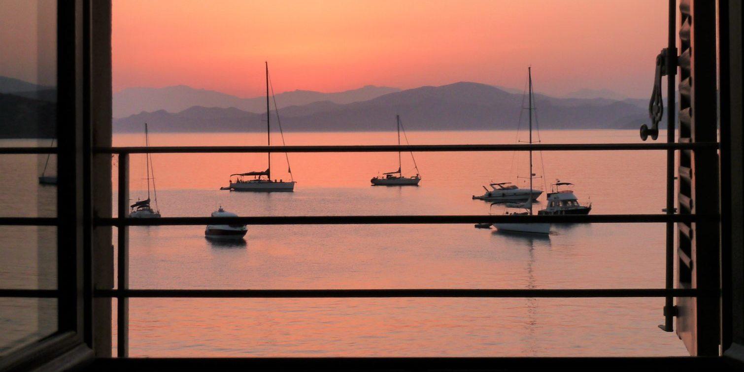 Hotel Perla Rossa Ile Rousse Corsica Frankrijk SkiMaquis OntdekCorsica zeezicht zonsondergang boten bergen rozerood licht