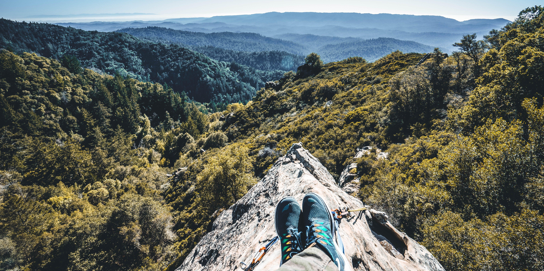 Hiking wandelen persoon-zittend-op-een-klif wandelschoenen fotograaf Joseph-Barrientos